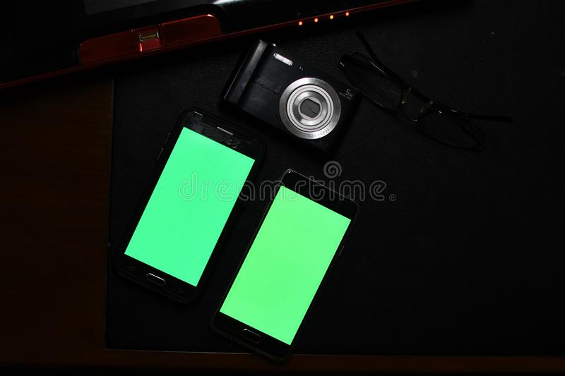 Office setup with Mobile phones with green screen. Office setup with Green screen shown on android mobile phone for further processing and photo editing. Green stock image