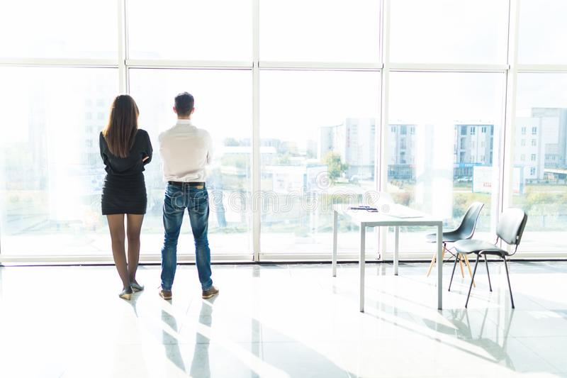 Office staff is discussing something by the window standing with their backs. Team work. stock photos