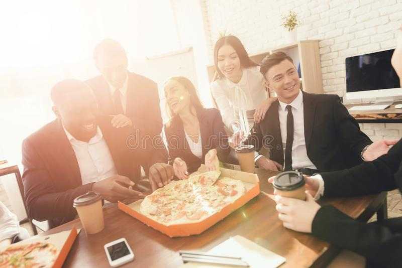 The office staff eat pizza and drink coffee in the business office. They have a break in their work. They are resting royalty free stock photos