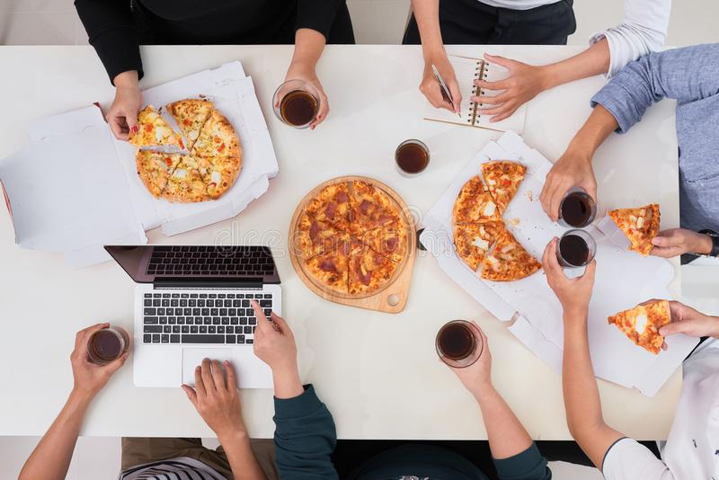 The office staff eat pizza and drink coffee in the business office. They have a break in their work. They are resting. royalty free stock photo