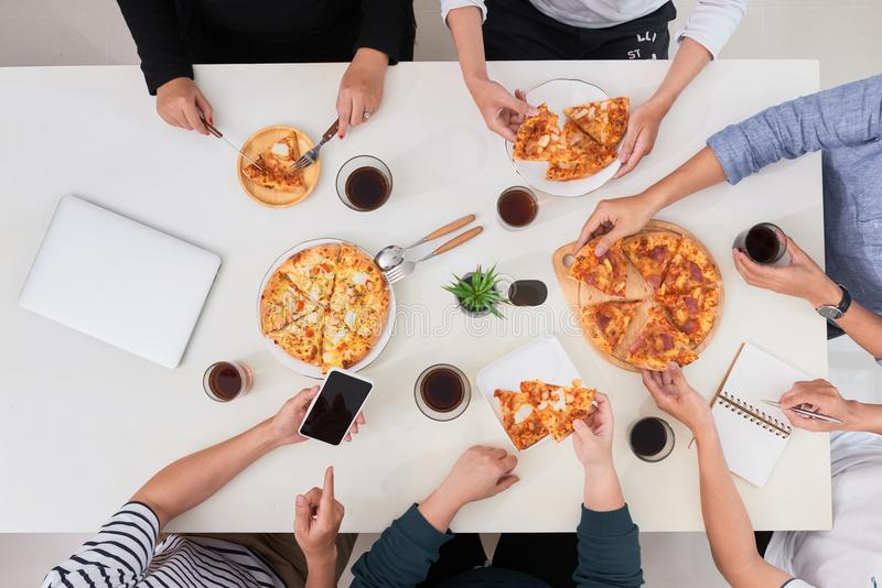 The office staff eat pizza and drink coffee in the business office. They have a break in their work. They are resting. stock photography
