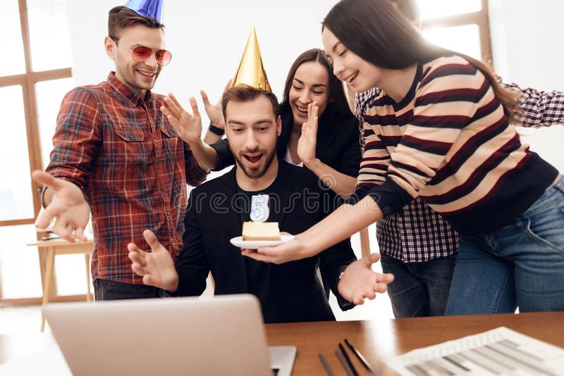 The office staff surprises their manager. They celebrate the anniversary of the company. They are dressed in holiday caps royalty free stock images