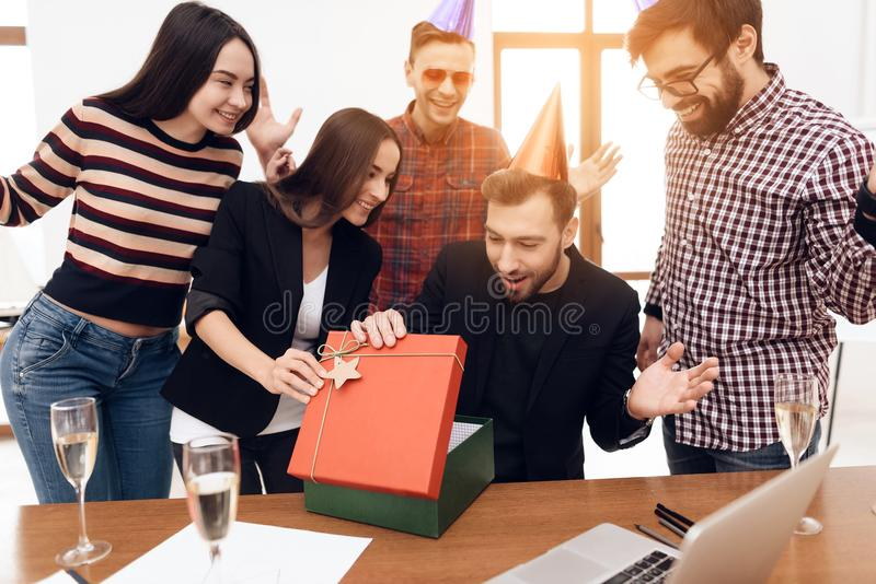 The office staff surprises their manager. They celebrate the anniversary of the company. They are dressed in holiday caps stock photography