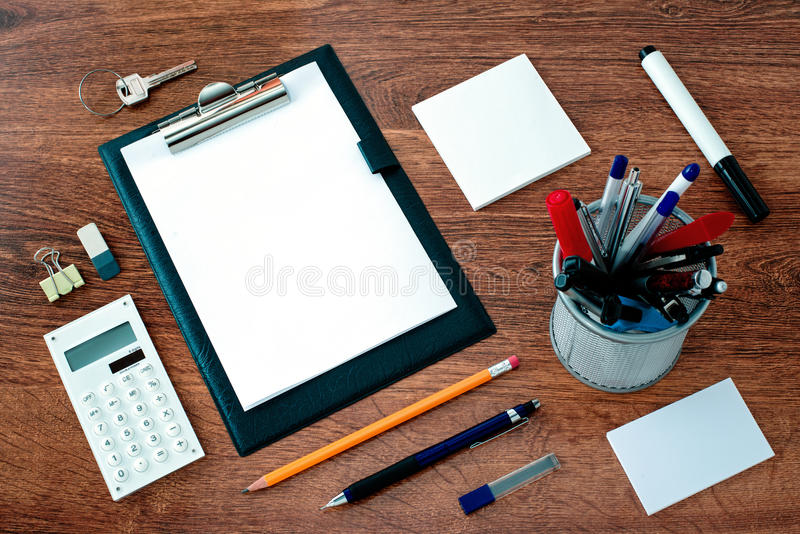 Office Supplies Arranged Around Clipboard on Desk stock photography