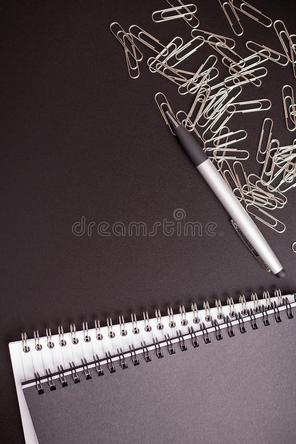 Office supplies ballpen with notepad and binder clips. On black table stock photos