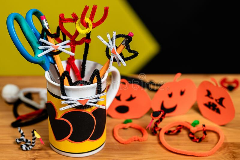 Office supplies decorated for Halloween in a Coffee Mug that says BOO. The table surface is covered in other halloween crafts. Snakes and Jack-O-Lanterns and stock photo