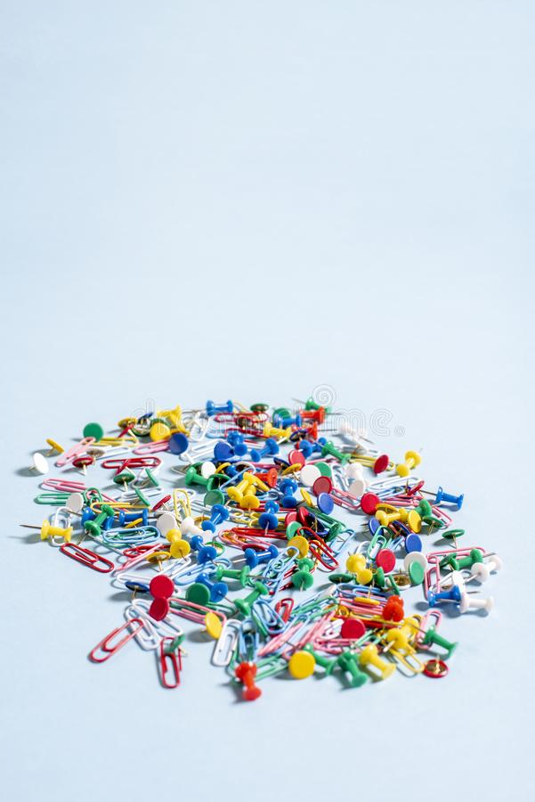 Office supplies in the form of colored buttons and paper clips. On blue background stock photography