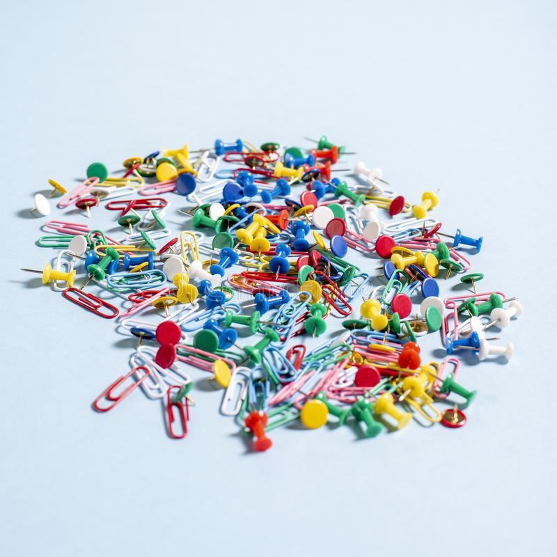 Office supplies in the form of colored buttons and paper clips. On blue background royalty free stock photography