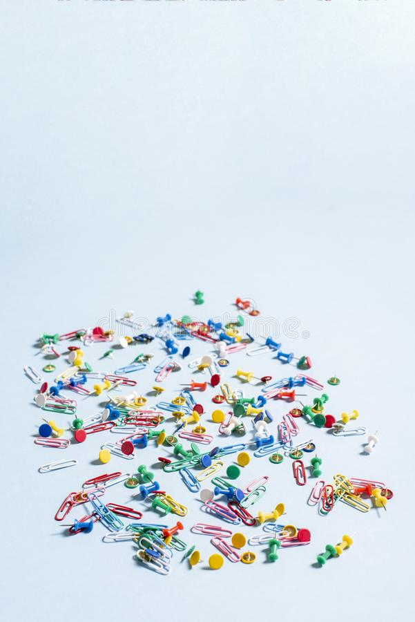Office supplies in the form of colored buttons and paper clips. On blue background royalty free stock photos