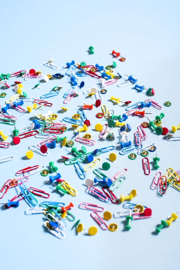 Office supplies in the form of colored buttons and paper clips. On blue background royalty free stock photo