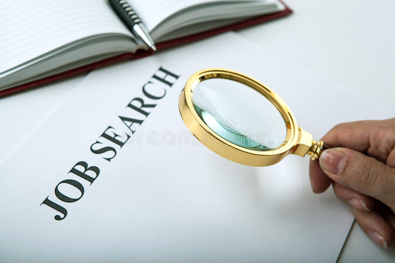 Office supplies and job search. Inscription job search and a hand holding a magnifying glass stock photography
