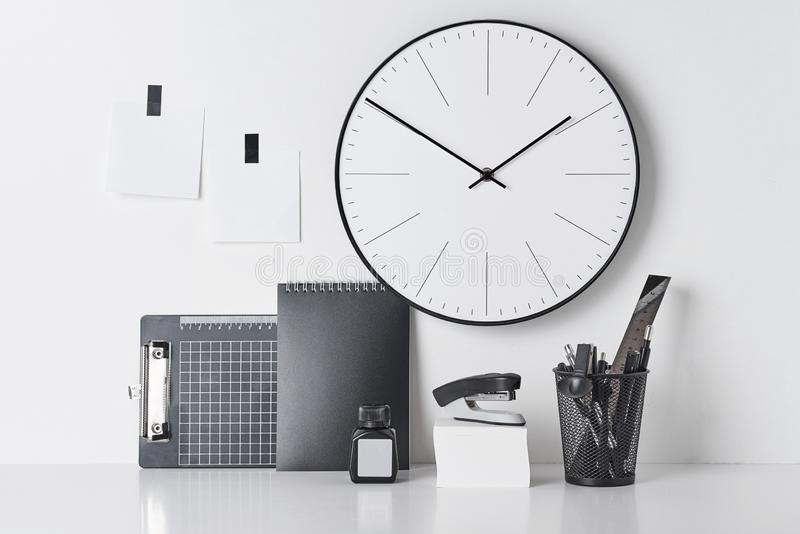 Office supplies, sticky and round clock on white. Office supplies, sticky blanks and round clock on white wall, front view. Office workplace desk royalty free stock images