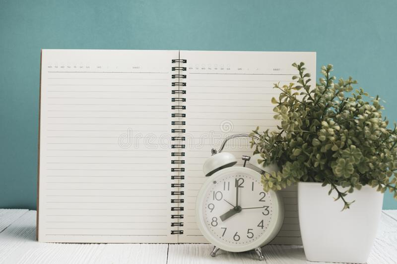 Office supplies or office work essential tools items on wooden desk in workplace, notebook, alarm clock and little tree with green. Wall background copy space stock images