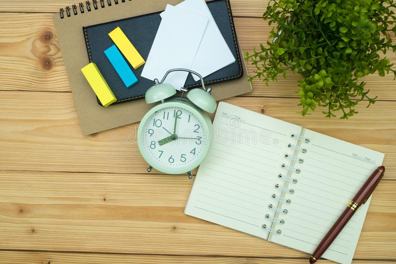 Office supplies or office work essential tools items on wooden desk in workplace, pen with notebook and alarm clock, top view. Office supplies or office work stock photos