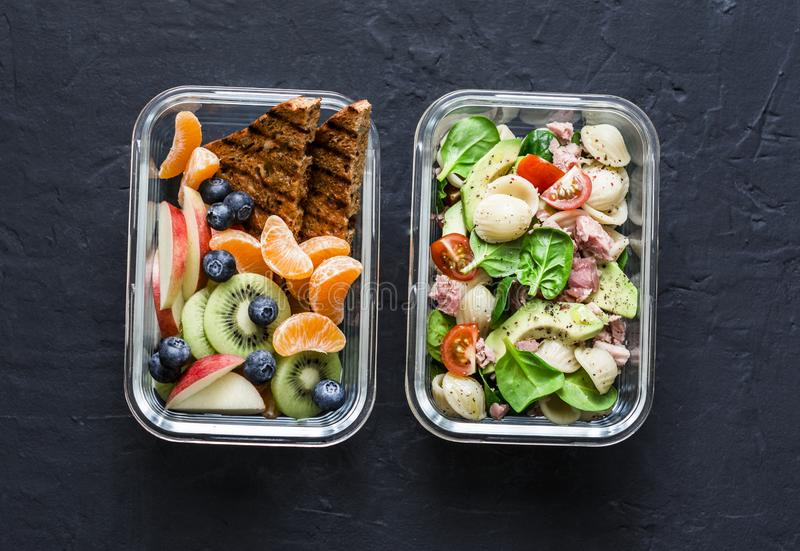 Office sweet and savory food lunch box. Pasta, tuna, spinach, avocado salad and fruit lunch box on dark stock image