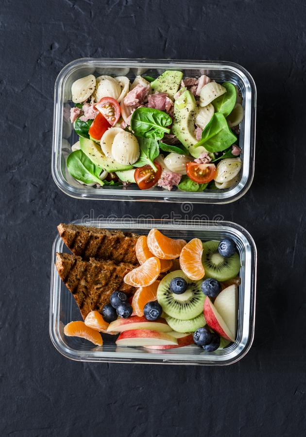 Office sweet, savory food lunch box. Pasta, tuna, spinach, avocado salad and fruit, peanut butter sandwiches lunch box on dark. Office sweet and savory food royalty free stock images