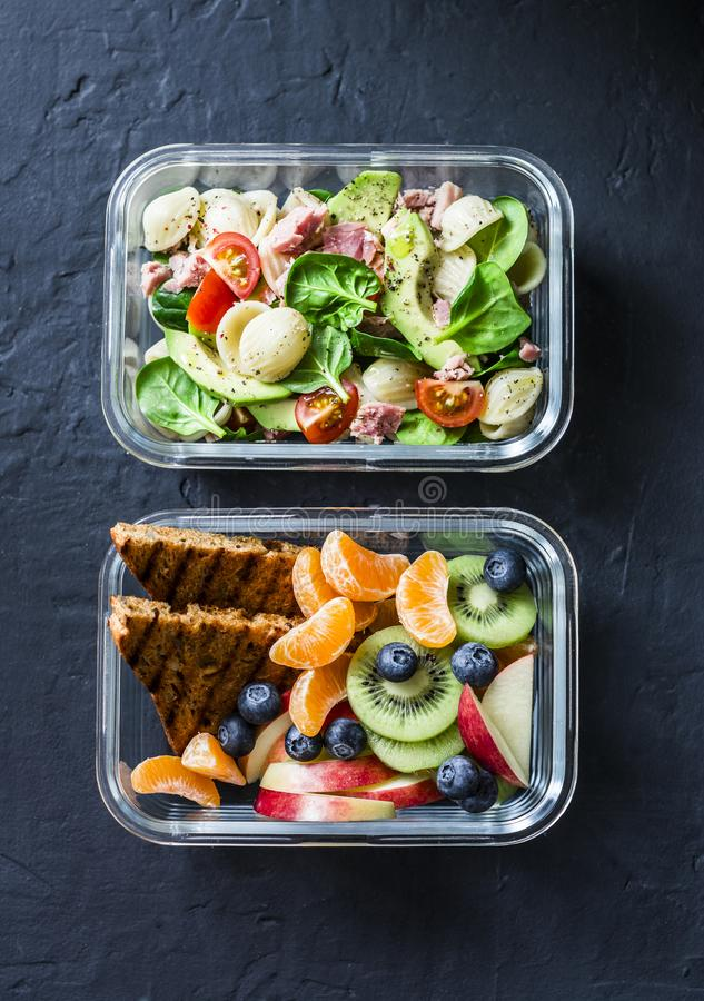 Office sweet and savory food lunch box. Pasta, tuna, spinach, avocado salad and fruit, peanut butter sandwiches lunch box on dark royalty free stock image