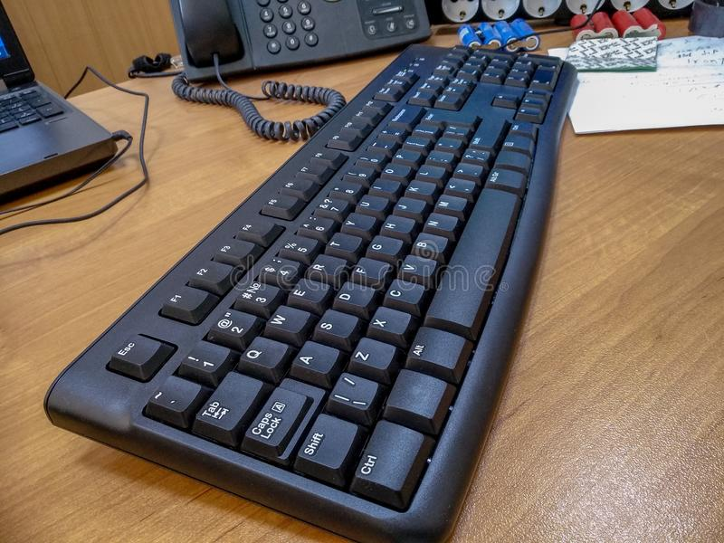 Office table with black computer wired keyboard. Closeup stock photography