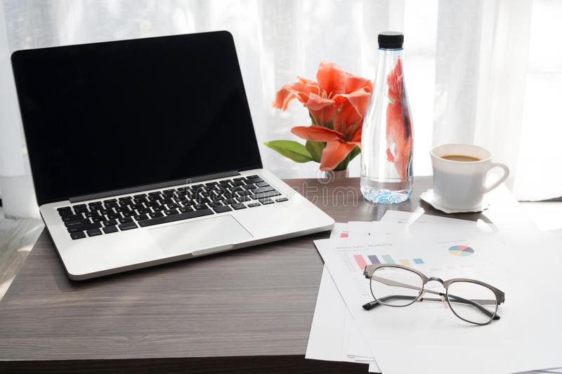 Office table with blank screen on laptop and beautiful flower , royalty free stock photo
