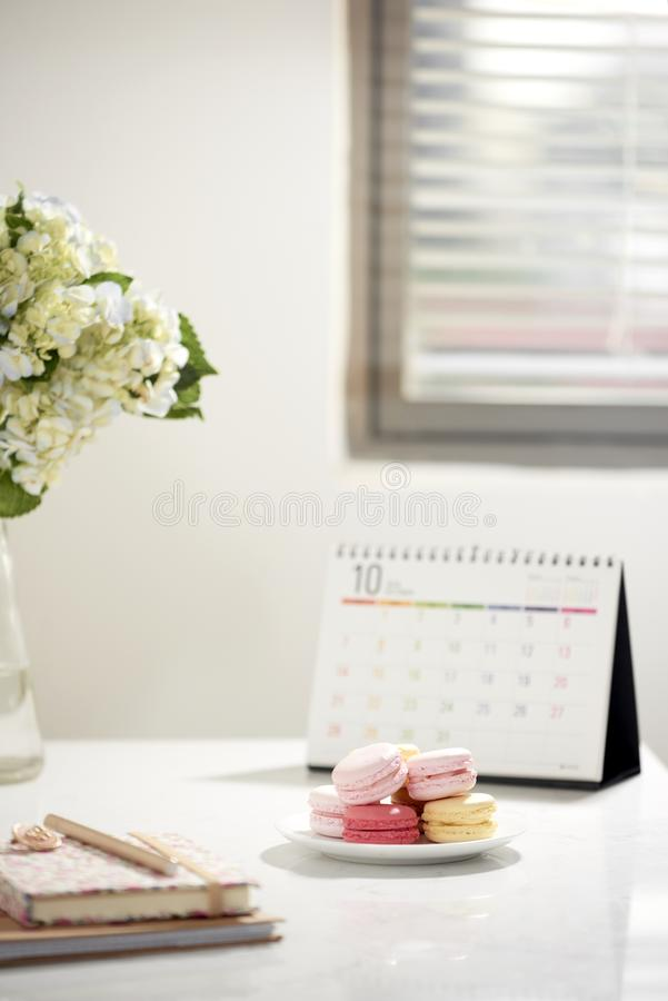 Office table desk. Feminine desk workspace frame with calendar, diary, hortensia bouquet and macaron on white background. ideas, stock photo