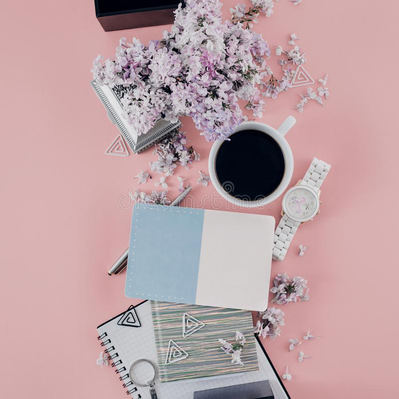 Office table desk flowers Top view Flat lay Home office workspace Women office accessories pink background. Office table desk with cup coffee, notebook, bouquet royalty free stock photo