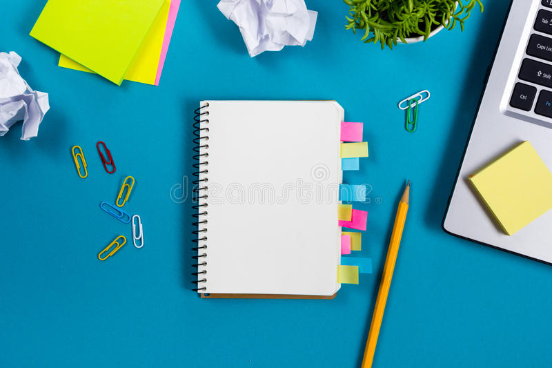 Office table desk with set of colorful supplies, white blank note pad, cup, pen, pc, crumpled paper, flower on blue stock photo