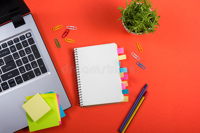 Office table desk with set of colorful supplies, white blank note pad, cup, pen, pc, crumpled paper, flower on red stock photo