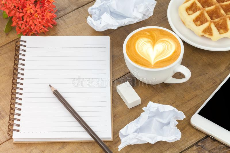 Office table desk with set of colorful supplies, white blank note pad, cup, pencil, smartphone, crumpled paper, flower on wood stock images