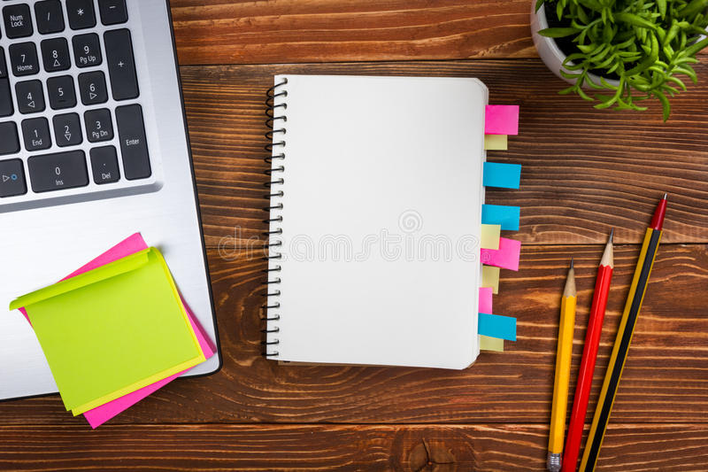 Office table desk with supplies, white blank note pad, cup, pen, pc, crumpled paper, flower on wooden background. Top royalty free stock images