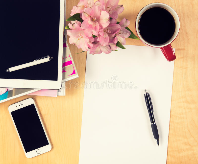 Office table with digital tablet, smartphone empty sheet of paper and cup of coffee. View from above. With copy space