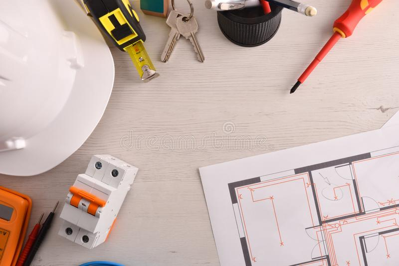 Office table of electrical engineer with installation project and tools stock photography
