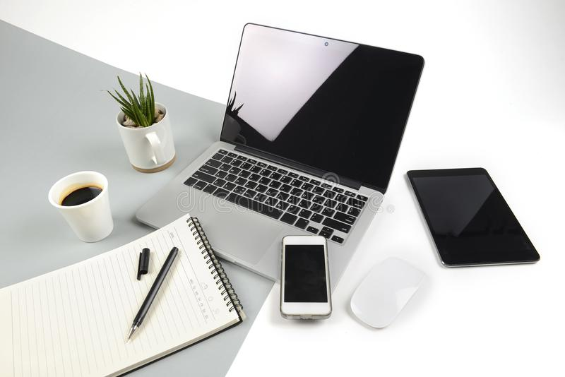 Office table with laptop computer, notebook, digital tablet and smartphone on modern two tone white and grey background royalty free stock images