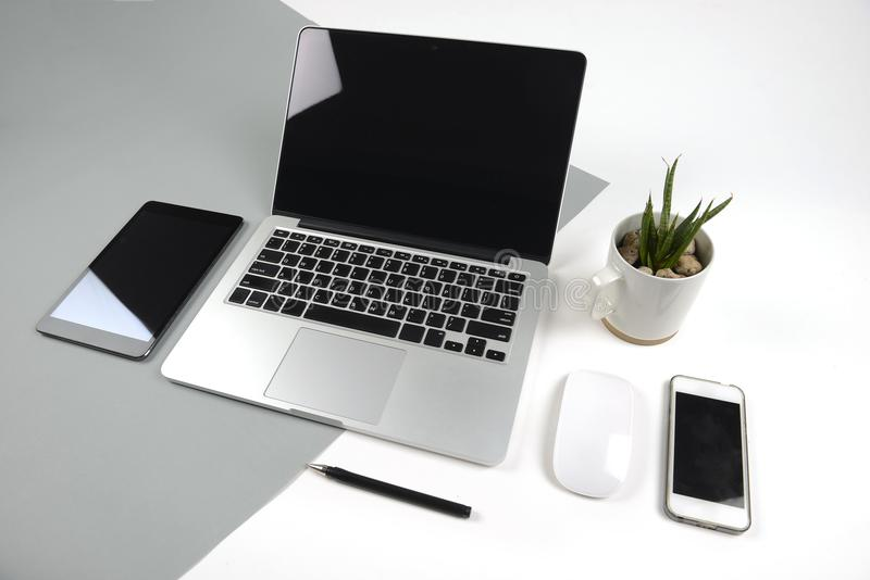 Office table with laptop computer, notebook, digital tablet and smartphone on modern two tone white and grey background royalty free stock photography