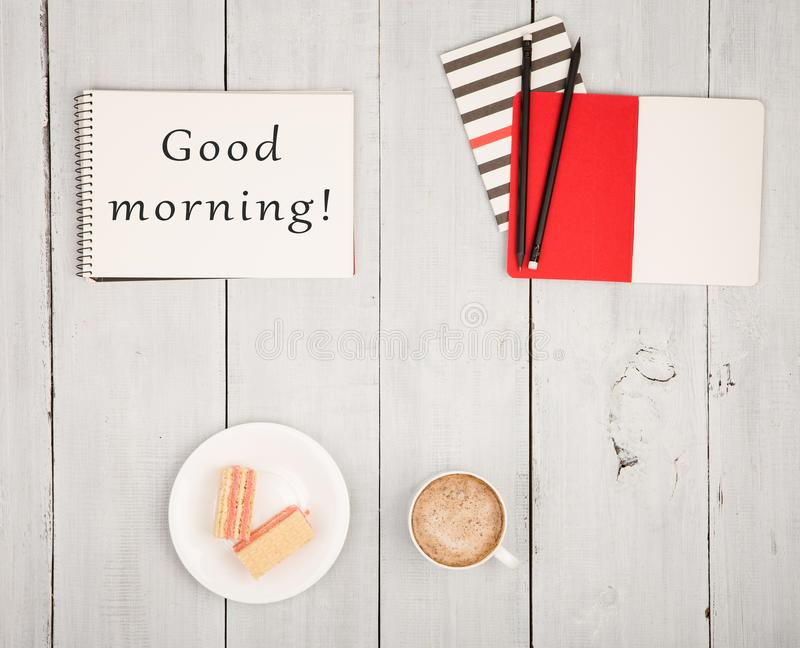 Office table with notepads and text & x22;Good morning!& x22;, cup of coffee and waffles. On white wooden background stock photo