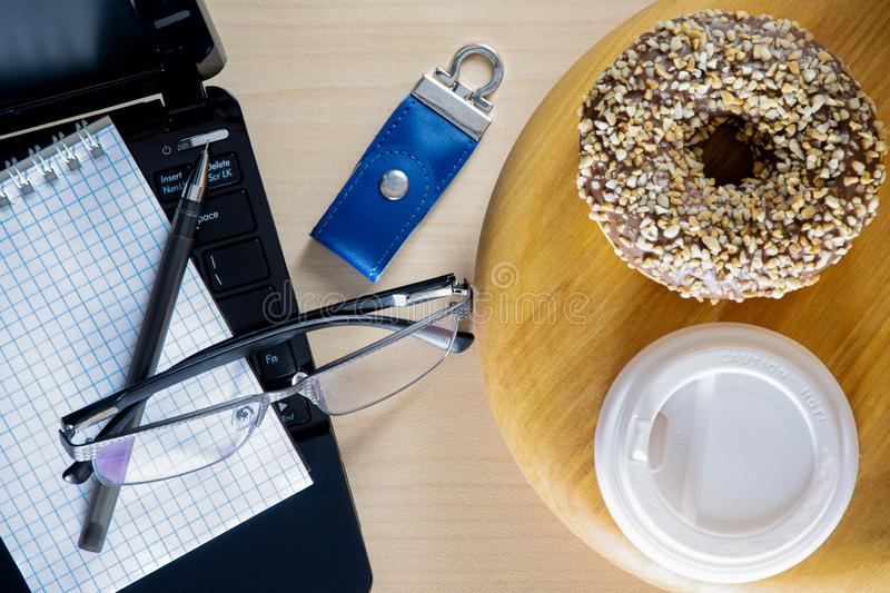 Office table. An open laptop, a notebook with a pen, a cup of coffee on a tray. Wooden table. royalty free stock photography