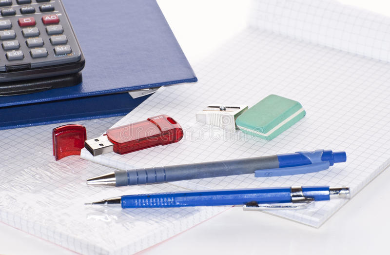 Office tools. Detail of some office tools as pens,rubber,sharpner,pencils,pen drive,calculator,note and file holder royalty free stock image