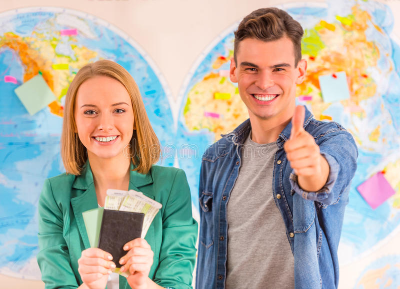 Office Travel Agency. Portrait of a young men and women chooses a place to travel through area, sitting in office travel agency stock images