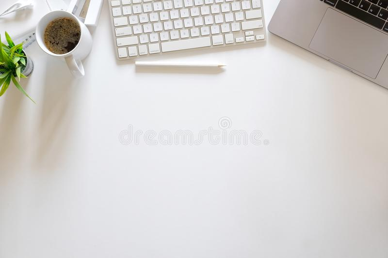 Office white desk table with laptop computer, supplies and coffee mug. Top view workspace and copy space stock image