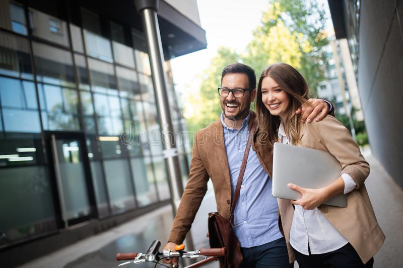 Office woman with business man couple enjoying break while talking flirting outdoor. Happy office women with business men couple enjoying break while talking stock photo