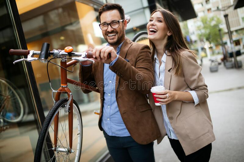 Office woman with business man couple enjoying break while talking flirting outdoor royalty free stock image
