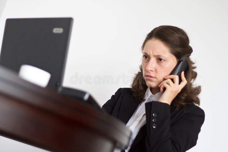 Office woman concentrated. Overworked office woman concentrated at her desk talking business on the phone royalty free stock photography