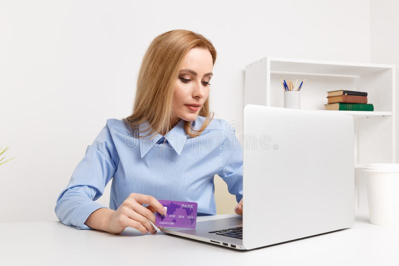Office woman holding purple credit card and making shopping online at her workplace. Office woman holding purple credit card and making shopping online at her stock image