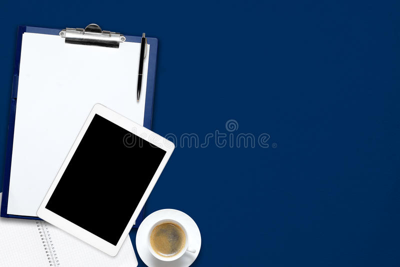 Office work desk table with laptop, tablet, cup of coffee and blank note book on blue background. Office black work desk table with laptop, tablet, cup of stock image
