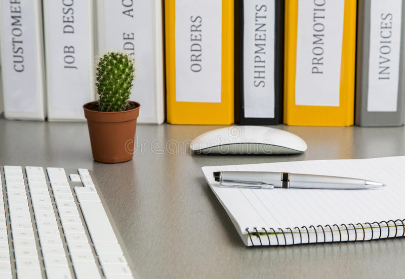 Office work space on grey desk with cactus and stock image