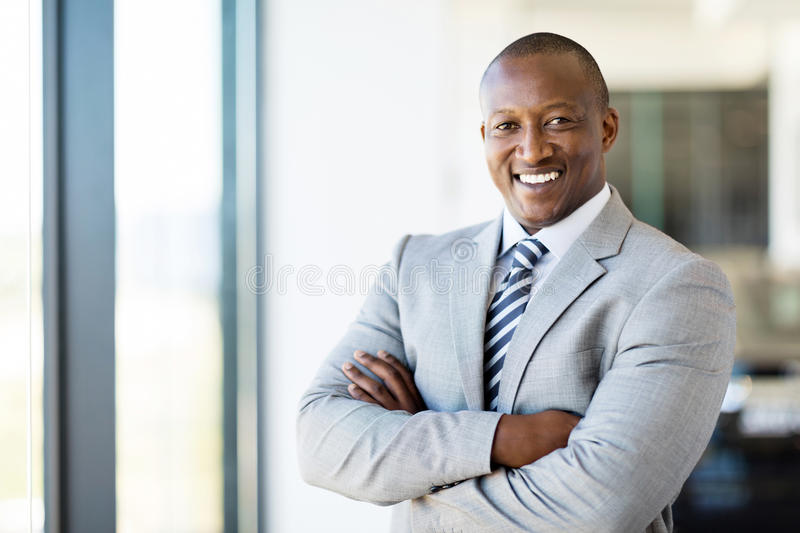 Office worker arms folded. Cheerful african american office worker with arms folded stock photo