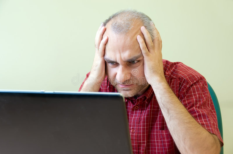Office worker broken down. Office worker gone to pieces at the desk with laptop royalty free stock image