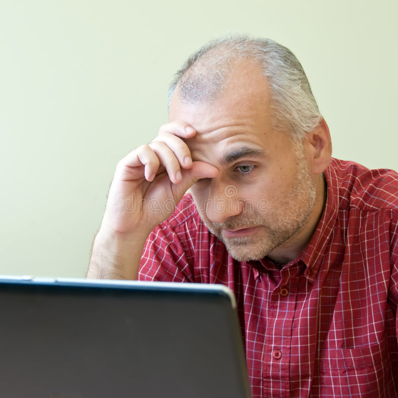Office worker broken down. Office worker gone to pieces at the desk with laptop stock image
