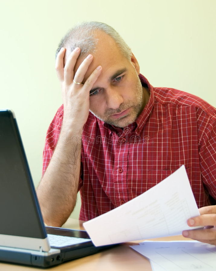 Office worker broken down. Office worker gone to pieces at the desk with sale report royalty free stock photo