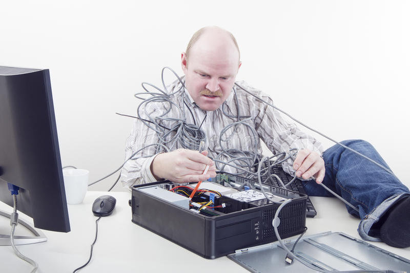 Office Worker with Computer Problems. Office worker / businessman in cables has computer problems stock photo