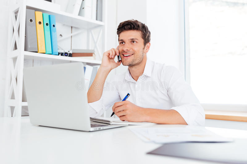 Office worker calling on the phone and using laptop royalty free stock photography